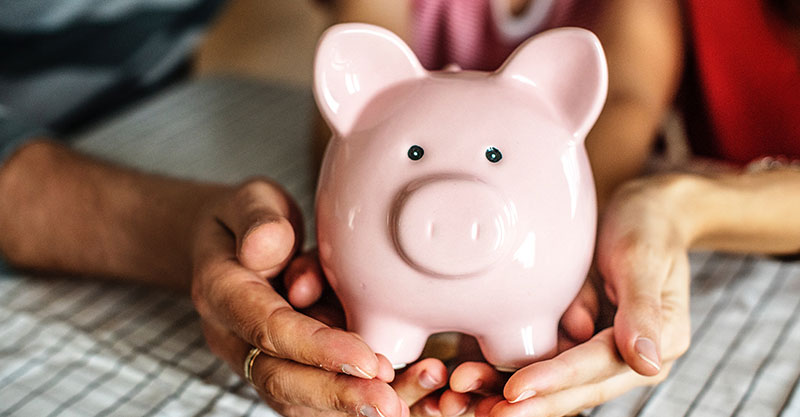 couple-holding-pink-piggy-bank
