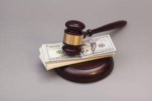 Law gavel on a stack of dollars isolated on gray