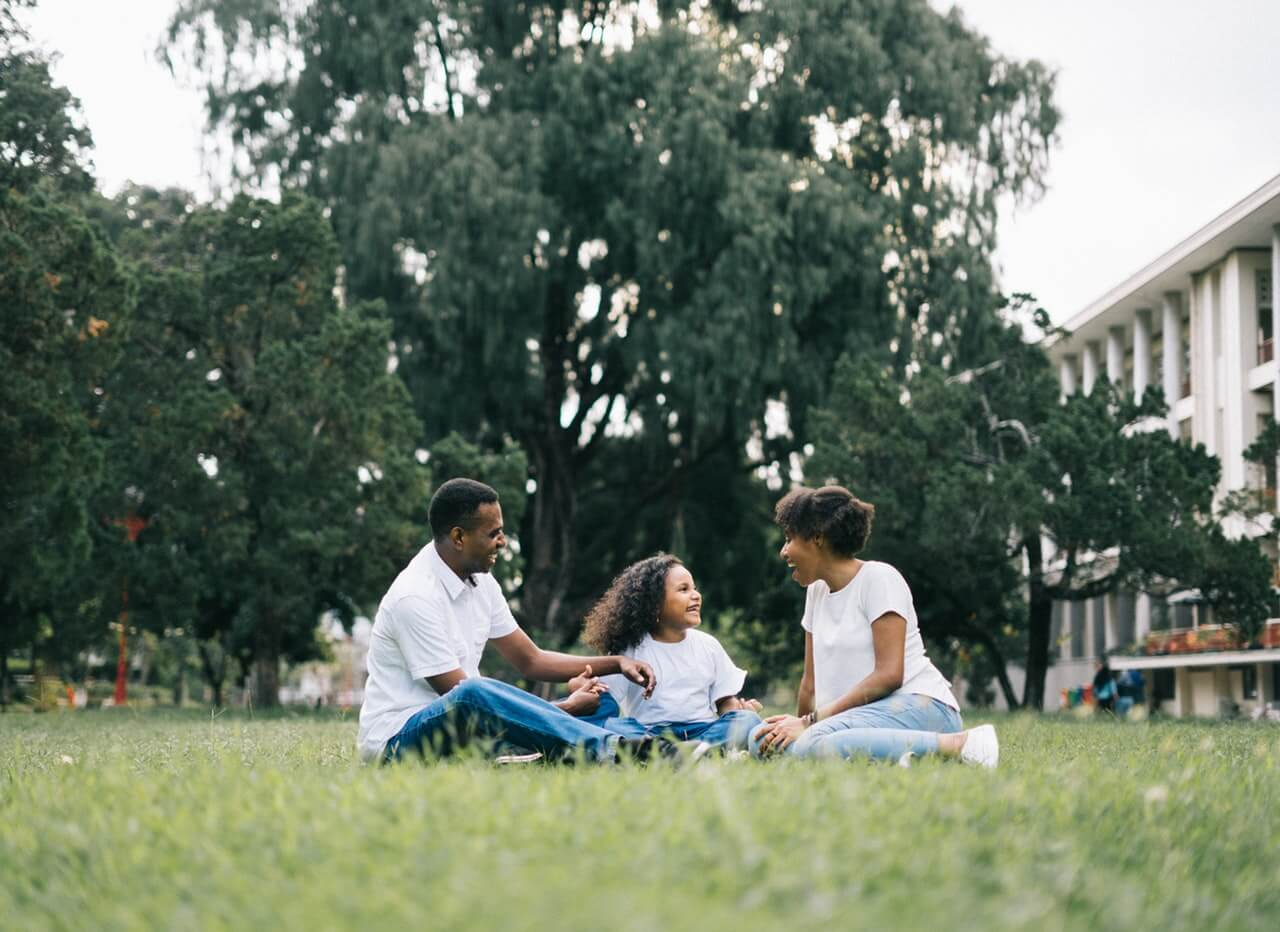 family-sitting-on-grass-near-building