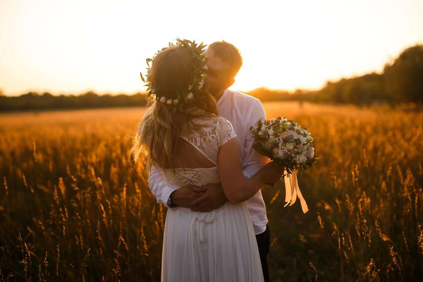 man-and-woman-standing-in-front-of-brown-grass-field-kissing