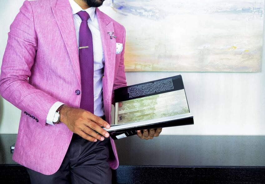 man-in-pink-suit-jacket-holding-book